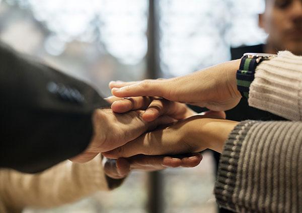 Die Mitglieder der WiGe eG halten die Hände in der Mitte übereinander
