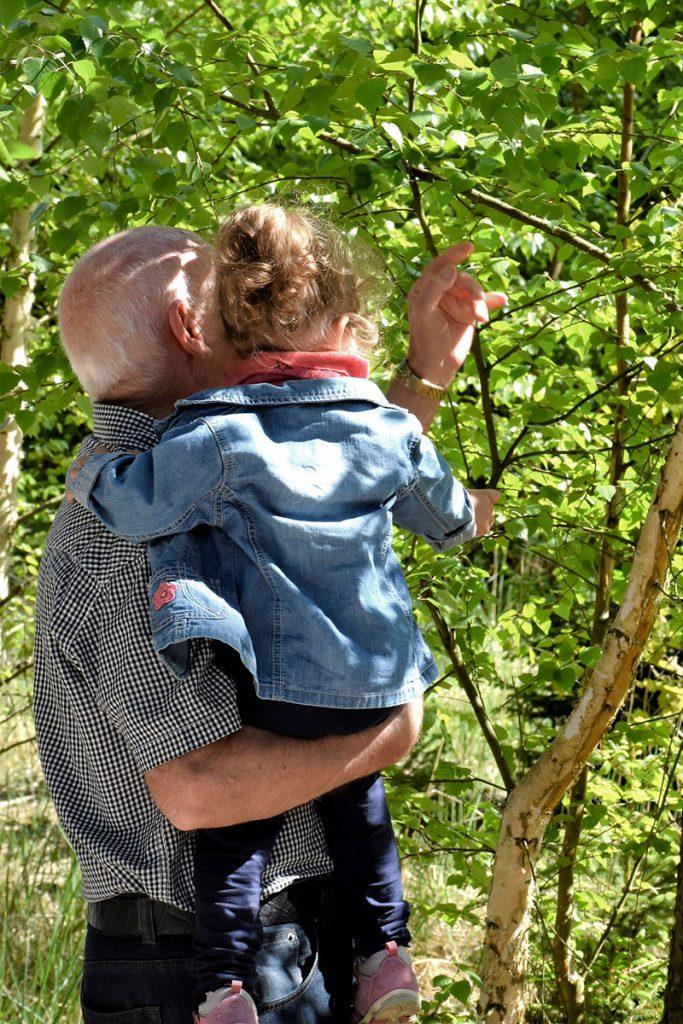 Ein Großvater hat seine Enkelin auf dem Arm und zeigt ihr einen Baum
